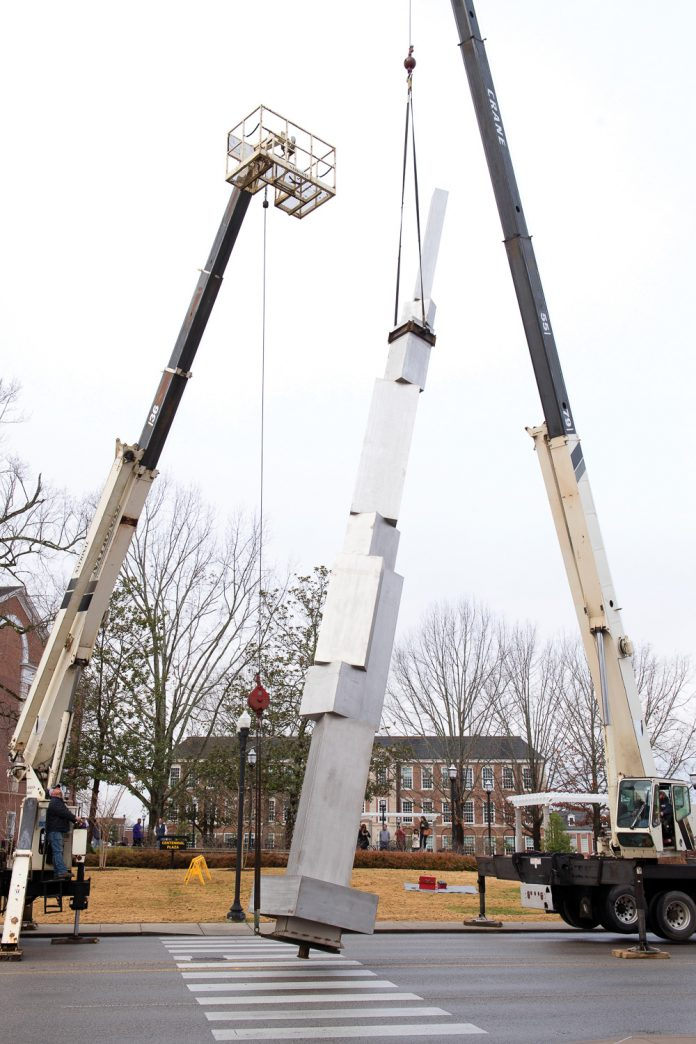 Ascension sculpture being lifted by two cranes for installation.